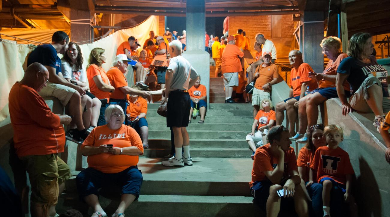 Fans gather in a shelter area at Memorial Stadium on Friday, Sept. 4, 2015, in Champaign, Ill., as lghtning and thunderstorms delayed the start of an NCAA college football game between Illinois and Kent State. (AP Photo/Bradley Leeb)