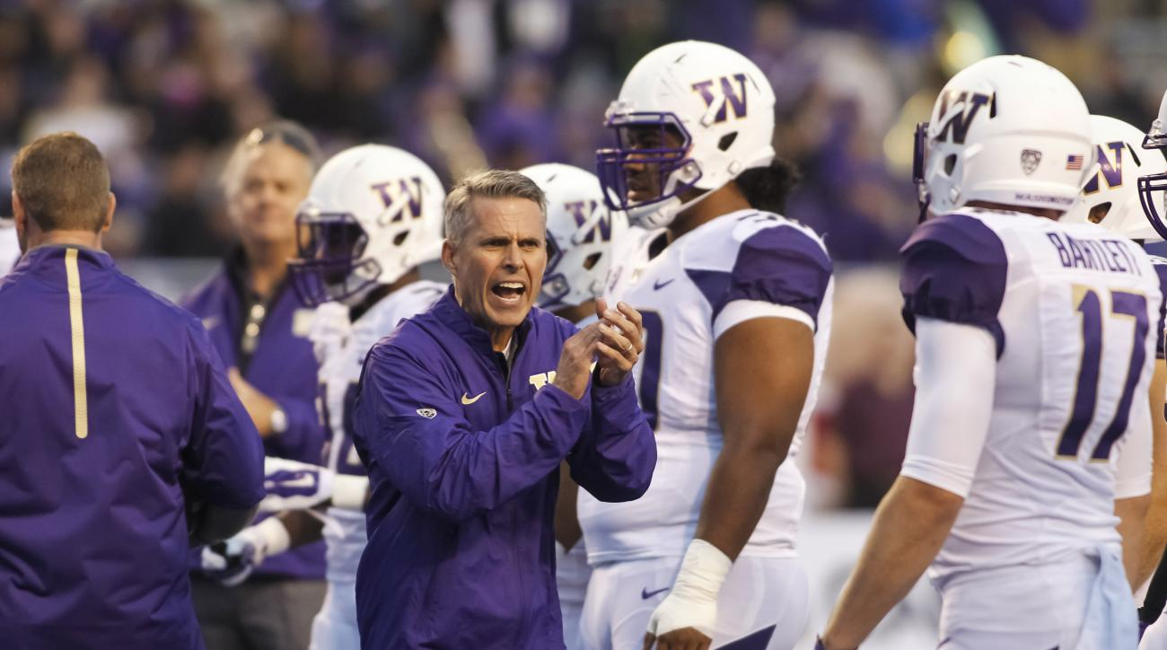 Washington coach Chris Petersen applauds as players warm up for an NCAA college football game against Boise State in Boise, Idaho, on Friday, Sept. 4, 2015. (AP Photo/Otto Kitsinger)