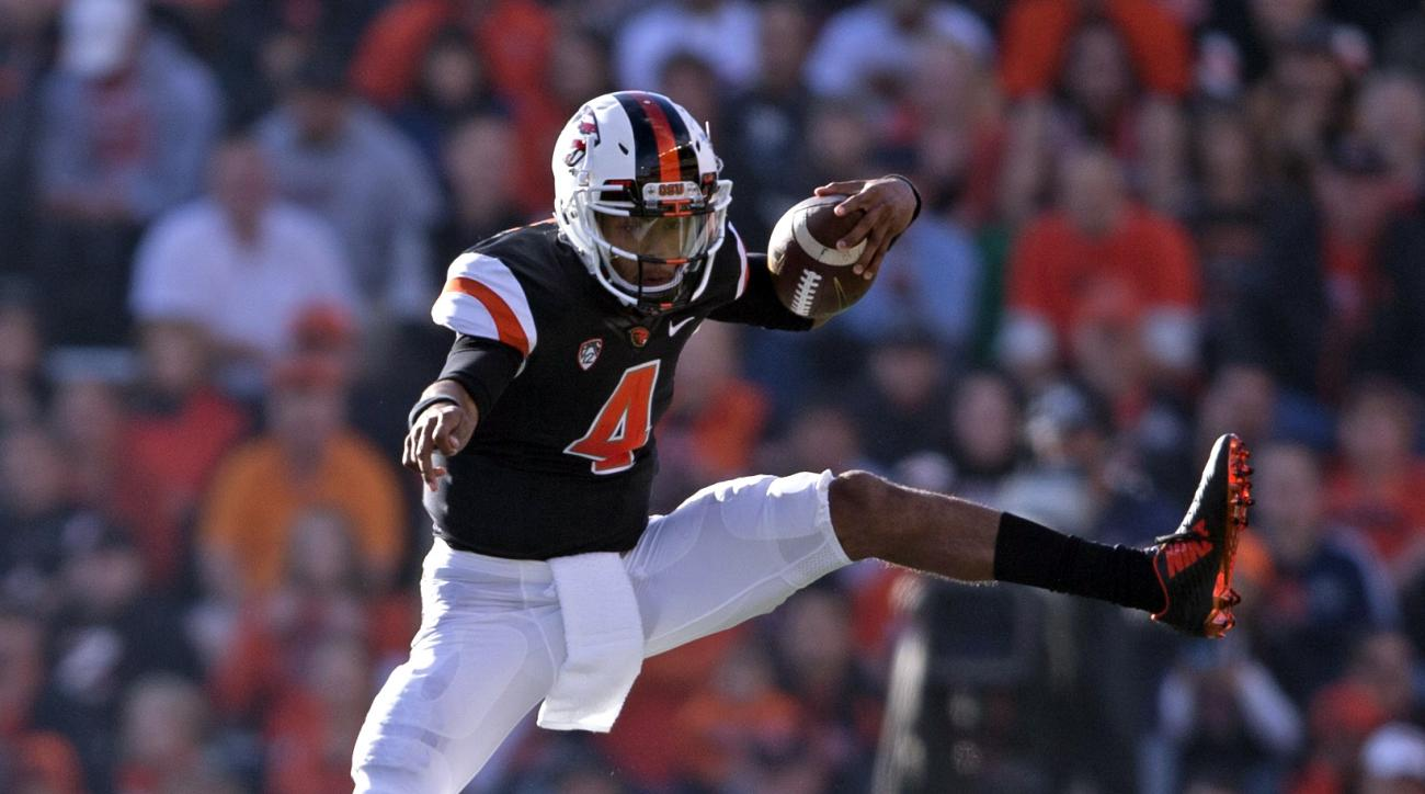 Oregon State quarterback Seth Collins leaps over Weber State's Josh Burton in the first half of an NCAA college football game Friday, Sept. 4, 2015, in Corvallis, Ore. Oregon State defeated Weber State 26-7. (AP Photo/Timothy J. Gonzalez)