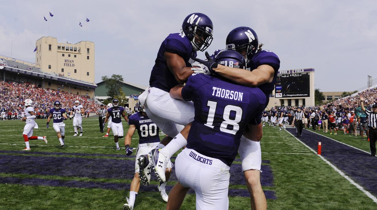 Northwestern quarterback Clayton Thorson (18) celebrates with running back Solomon Vault, left,  and wide receiver Mike McHugh (6) right, after he ran for a touchdown against Stanford during the second quarter of an NCAA college football game in Evanston,