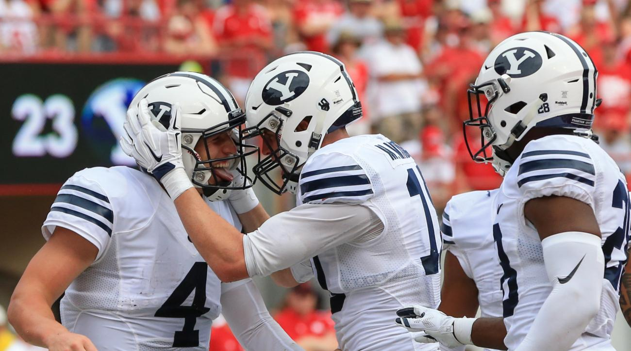 BYU quarterback Taysom Hill (4) and running back Adam Hine, right, celebrate with wide receiver Mitch Mathews (10) after Mathews scored a touchdown against Nebraska during the first half of an NCAA college football game in Lincoln, Neb., Saturday, Sept. 5