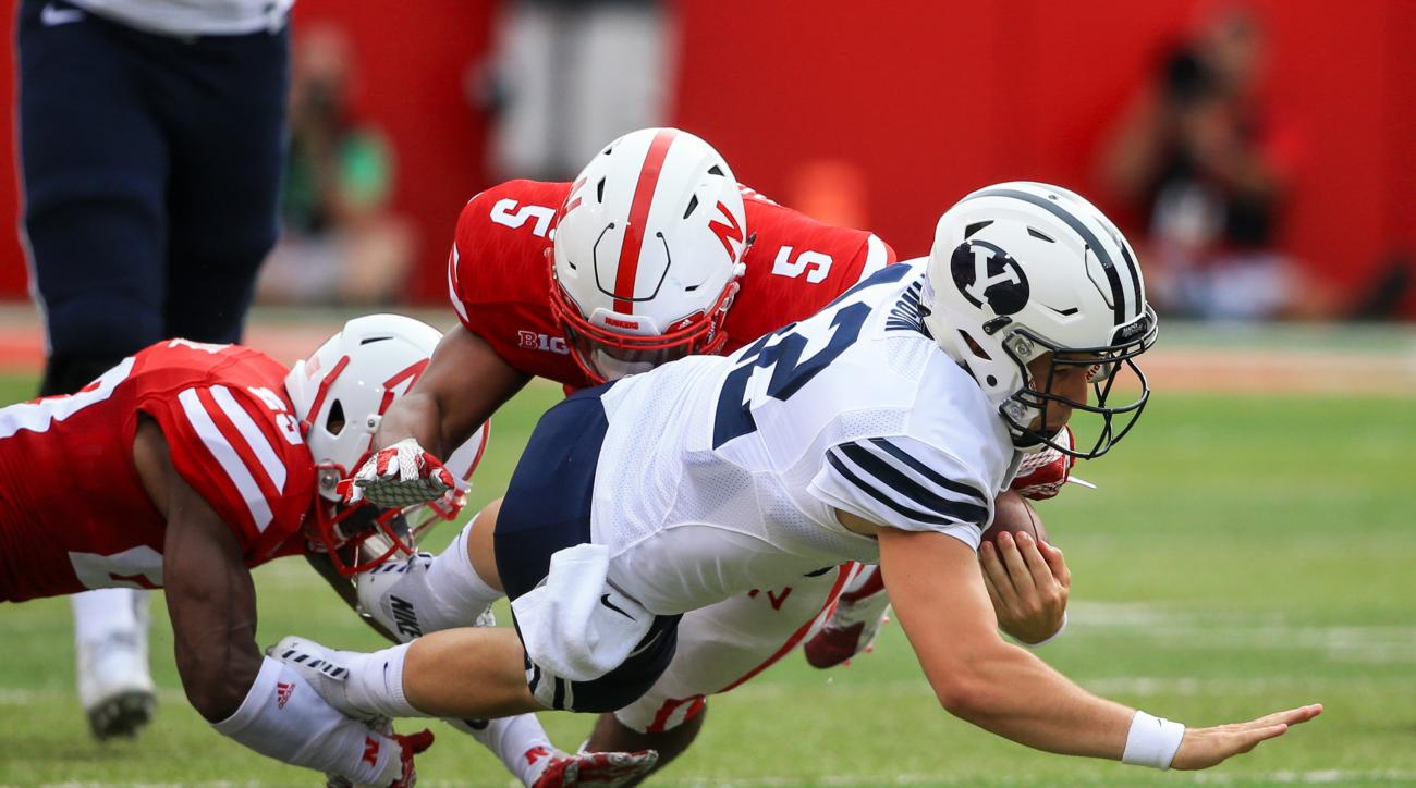 BYU quarterback Tanner Mangum (12) is tackled by Nebraska linebacker Dedrick Young (5) and cornerback Daniel Davie, left, during the first half of an NCAA college football game in Lincoln, Neb., Saturday, Sept. 5, 2015. (AP Photo/Nati Harnik)