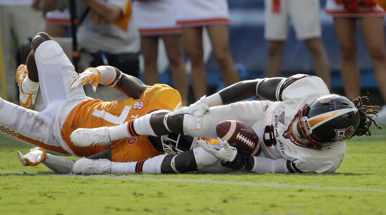 Bowling Green running back Travis Greene (8) grabs his knee as he is brought down by Tennessee defensive back Cameron Sutton (7) in the first half of an NCAA college football game Saturday, Sept. 5, 2015, in Nashville, Tenn. Greene was helped to the locke