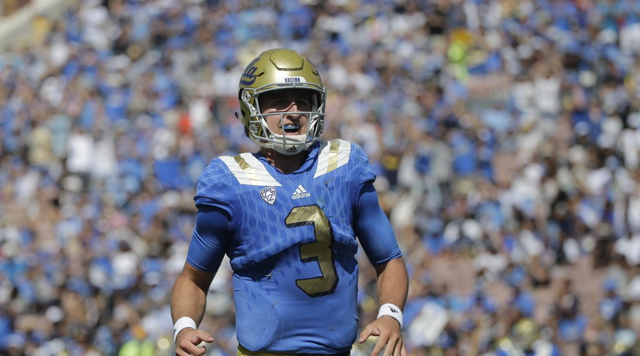 UCLA quarterback Josh Rosen celebrates a touchdown scored by Kenny Clark during the second half of an NCAA college football game against Virginia at the Rose Bowl, Saturday, Sept. 5, 2015, in Pasadena, Calif. UCLA won 34-16. (AP Photo/Jae C. Hong)