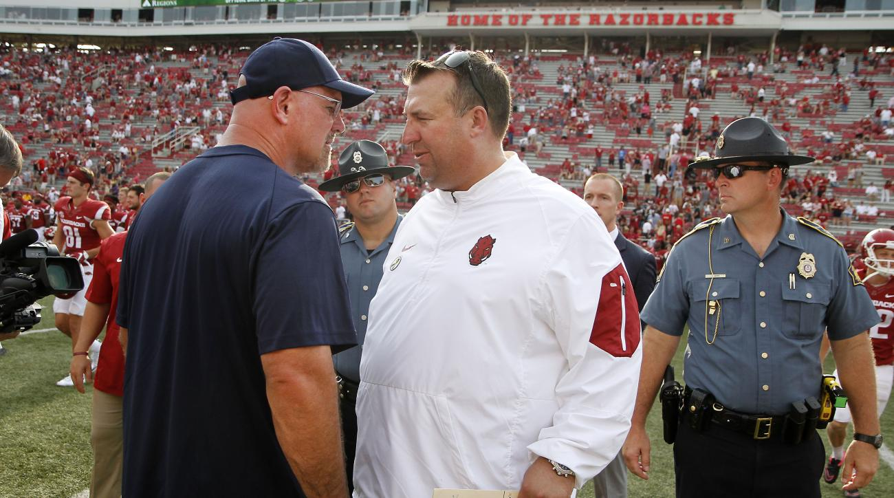 Arkansas coach Bret Bielema, right, exchanges works with UTEP coach Sean Kugler after their NCAA college football game against Fayetteville, Ark., Saturday, Sept. 5, 2015. Arkansas won 48-13.(AP Photo/Samantha Baker)