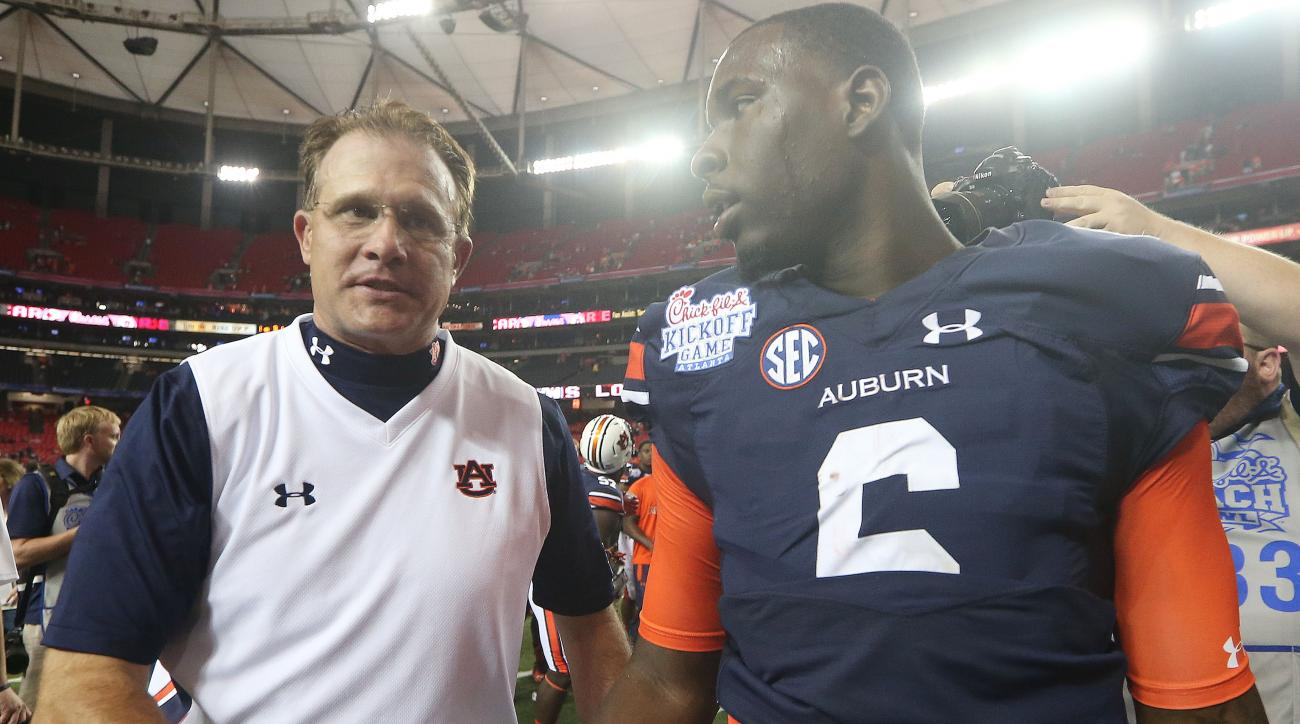 Auburn head coach Gus Malzahn, left, walks off the field with Auburn quarterback Jeremy Johnson (6) after the second half of an NCAA college football game against Louisville, Saturday, Sept. 5, 2015, in Atlanta. Auburn won 31-24. (AP Photo/John Bazemore)