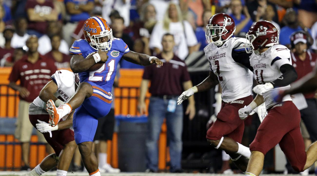 Florida running back Kelvin Taylor (21) runs past the New Mexico State defense including Terrill Hanks (2) and defensive back Tre Wilcoxen (11) for a gain on a pass play during the first half of an NCAA college football game, Saturday, Sept. 5, 2015, in G