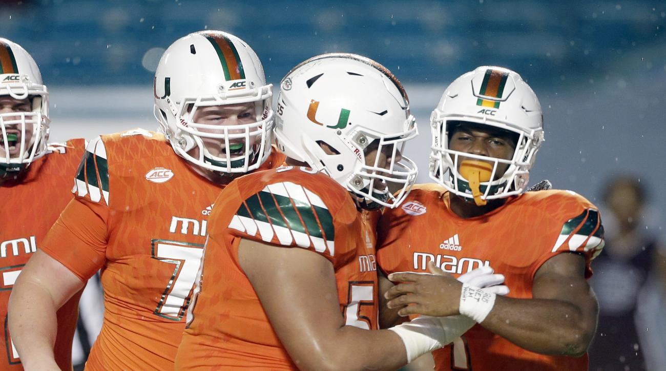 Miami defensive back Artie Burns, right, is congratulated by teammates after scoring a touchdown in the second half of an NCAA college football game against Bethune Cookman , Saturday, Sept. 5, 2015, in Miami Gardens, Fla. Miami won 45-0. (AP Photo/Alan D