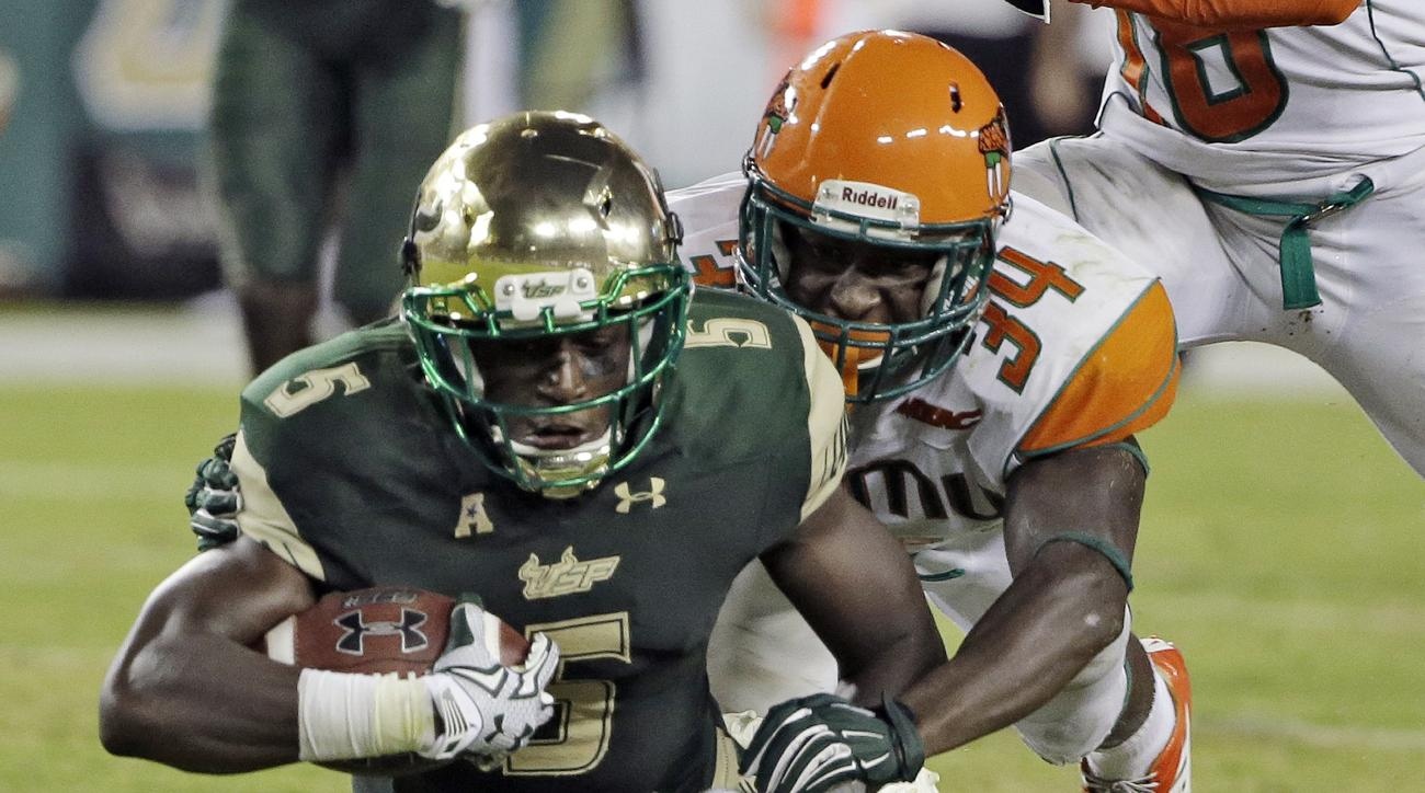 South Florida running back Marlon Mack (5) is stopped by Florida A&M defensive back John Boston (34) on a run during the third quarter of an NCAA college football game Saturday, Sept. 5, 2015, in Tampa, Fla. (AP Photo/Chris O'Meara)