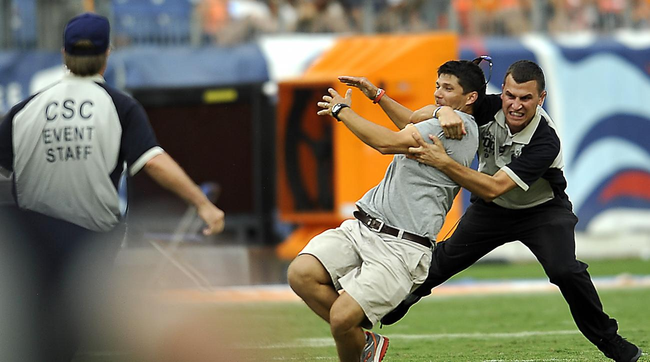 A fan, second from right, who ran onto the field is tackled by a security worker during a weather delay at an NCAA college football game between Tennessee and Bowling Green, Saturday, Sept. 5, 2015, in Nashville, Tenn. (Larry McCormack/The Tennessean via