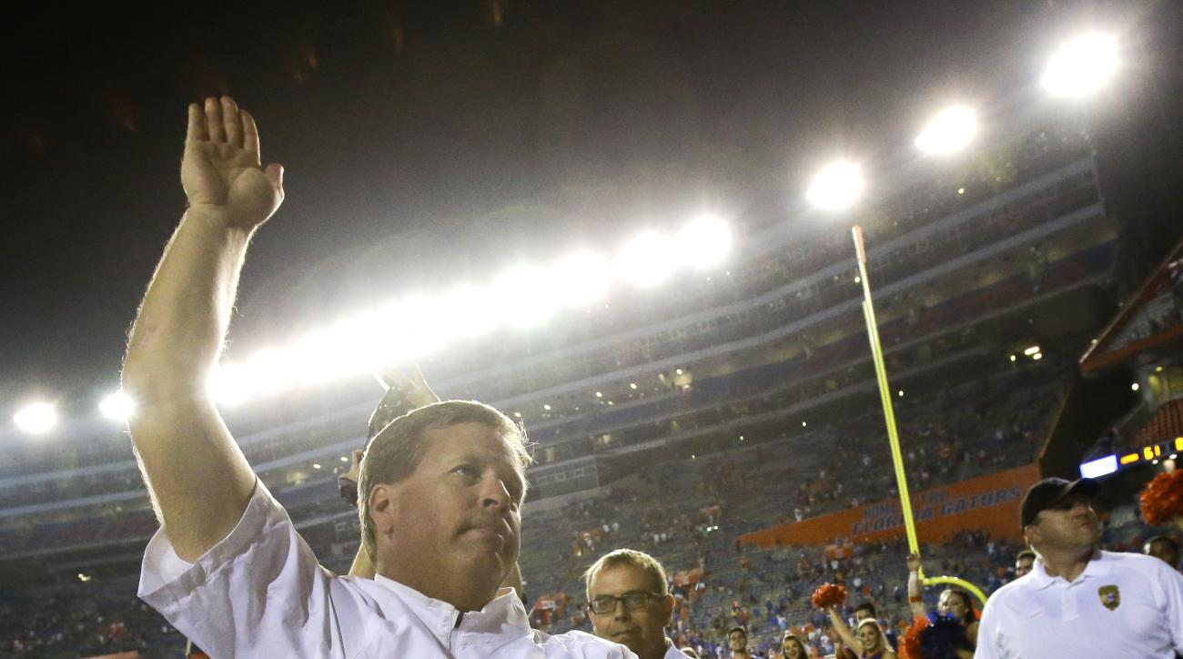 Florida head coach Jim McElwain celebrates with the gator chomp in front of fans after defeating New Mexico State 61-13 in an NCAA college football game Saturday, Sept. 5, 2015, in Gainesville, Fla.  (AP Photo/John Raoux)