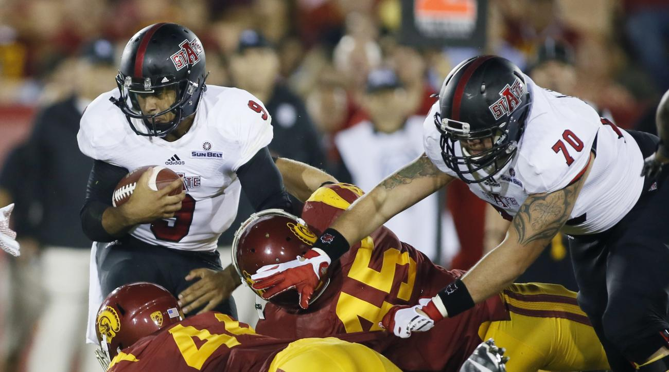 Arkansas State quarterback Fredi Knighten, left, avoids being brought down by Southern California defensive end Malik Dorton, bottom left, and Southern California defensive end Malik Dorton, center, while Arkansas State offensive lineman Kyle Harris tries