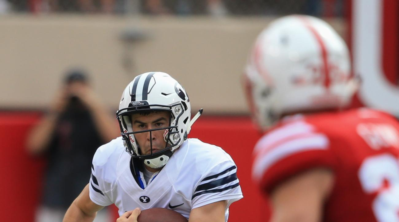 In this Sept. 5, 2015 photo, BYU quarterback Tanner Mangum (12) runs with the ball during the first half of an NCAA college football game against Nebraska in Lincoln, Neb. Taysom Hill's third season-ending injury in four years leaves freshman Tanner Mangu