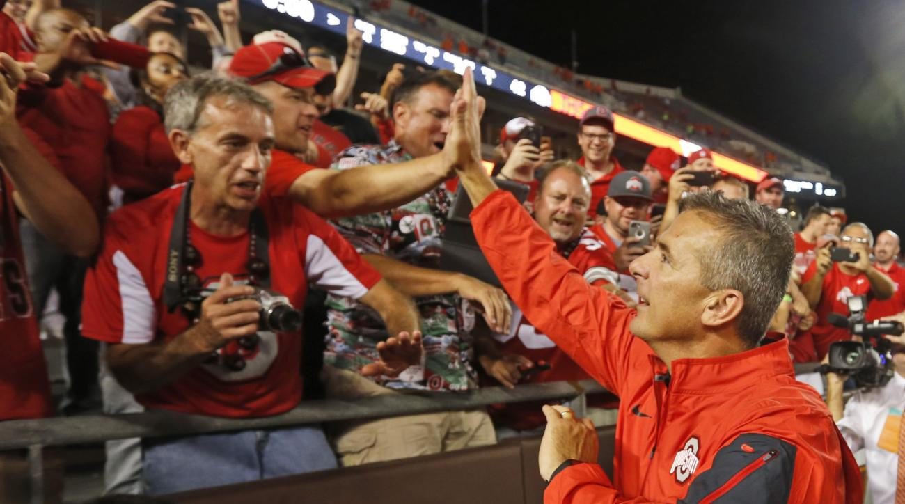 Ohio State head coach Urban Meyer celebrates with fans after they defeated Virginia Tech in an NCAA college football game in Blacksburg, Va., Monday, Sept. 7, 2015. Ohio State won 42-24. (AP Photo/Steve Helber)