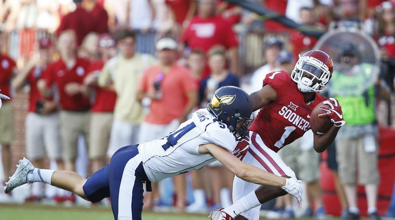 In this Sept. 5, 2015, photo, Oklahoma wide receiver Jarvis Baxter (1) is tackled by Akron linebacker Dylan Evans (54) during an NCAA college football game against Akron in Norman, Okla. To say Baxter's life has been somewhat of a whirlwind in recent week
