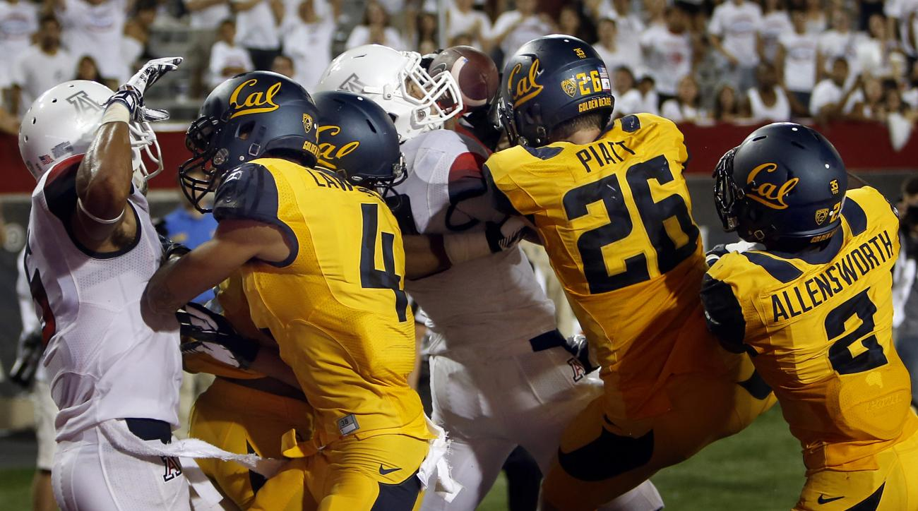 FILE - In this Sept. 20, 2014, file photo, Arizona running back Austin Hill, center in white, catches a pass for a touchdown in the middle of  California defenders including Kenny Lawler (4), Griffin Piatt (26) and Darius Allensworth (2) with no time left