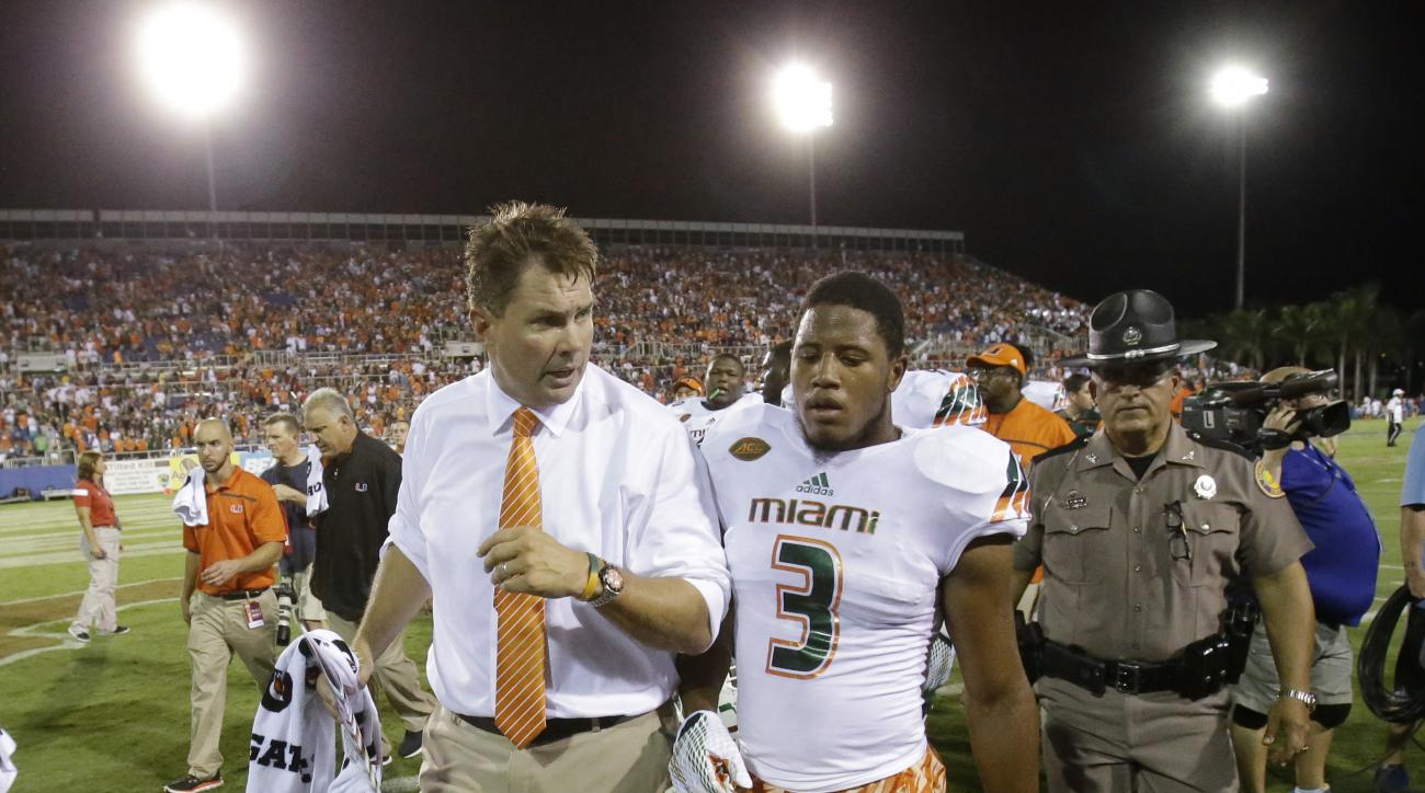 Miami head coach Al Golden, left, talks with defensive back Tracy Howard (3) as the team walks off the field during a weather delay in the first half of an NCAA college football game against Florida Atlantic, Friday, Sept. 11, 2015, in Boca Raton, Fla. (A