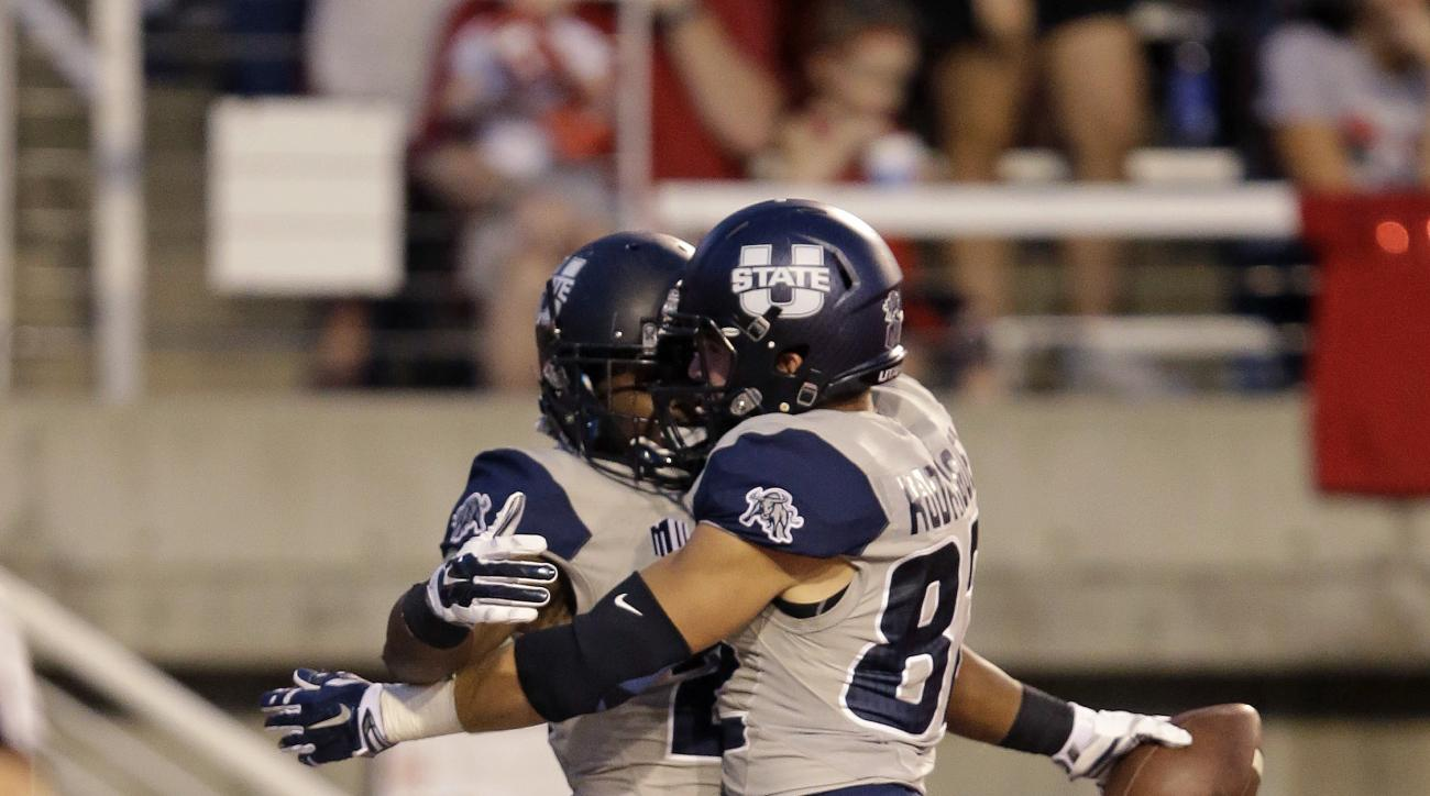 Utah State running back LaJuan Hunt, left, celebrates with wide receiver Andrew Rodriguez, right, after scoring against Utah in the second quarter during an NCAA college football game Friday, Sept. 11, 2015, in Salt Lake City. (AP Photo/Rick Bowmer)
