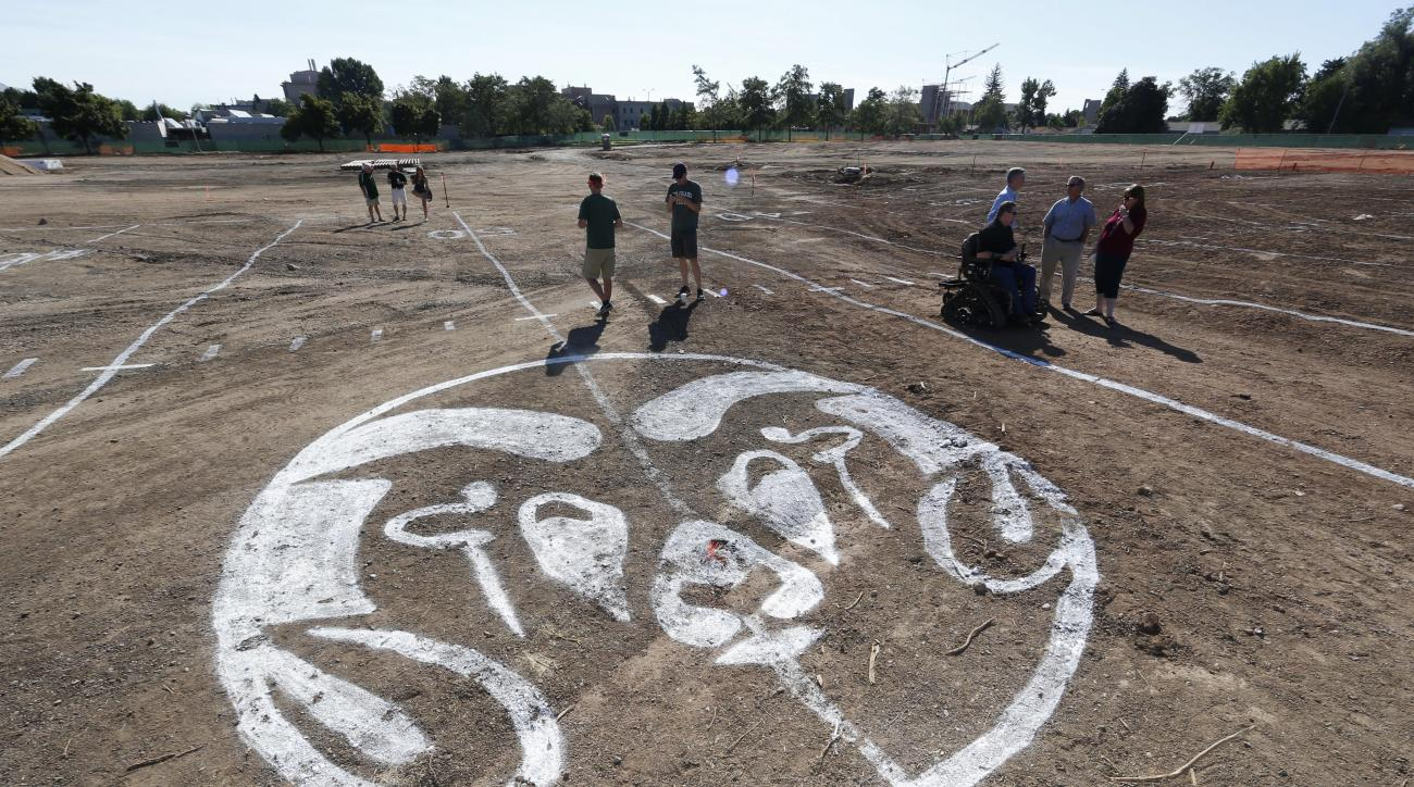 Donors take a look at the markings on the future 50-yard line of a new stadium during a ceremonial groundbreaking ceremony at Colorado State University to mark construction of an on-campus, multiple use facility Saturday, Sept. 12, 2015, in Fort Collins,