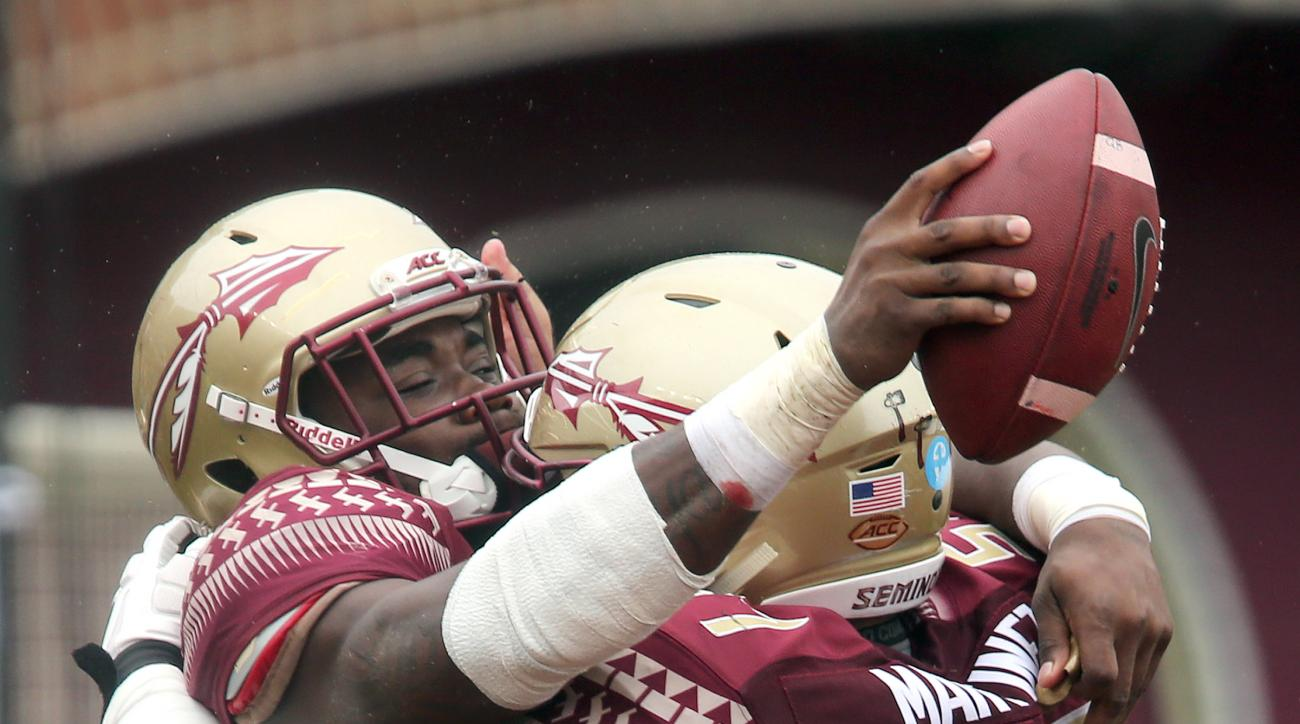 Florida State's Dalvin Cook, left, celebrates with Corey Martinez scoring on a 74-yard touchdown run against South Florida in the first quarter of an NCAA college football game, Saturday, Sept. 12, 2015 in Tallahassee, Fla. (AP Photo/Steve Cannon)