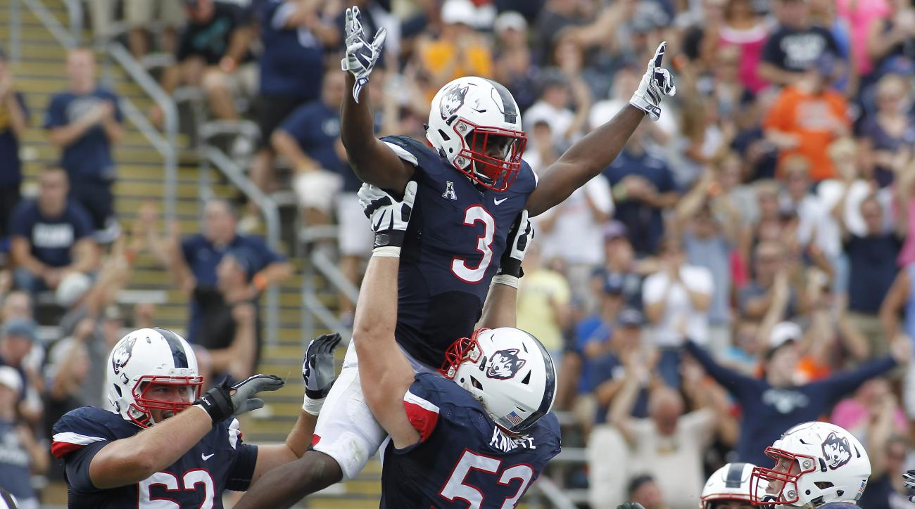 Connecticut running back Ron Johnson (3) is lifted in the air by offensive lineman Andreas Knappe after scoring a touchdown during the third quarter of an NCAA college football game against Army at Rentschler Field, Saturday, Sept. 12, 2015, in East Hartf