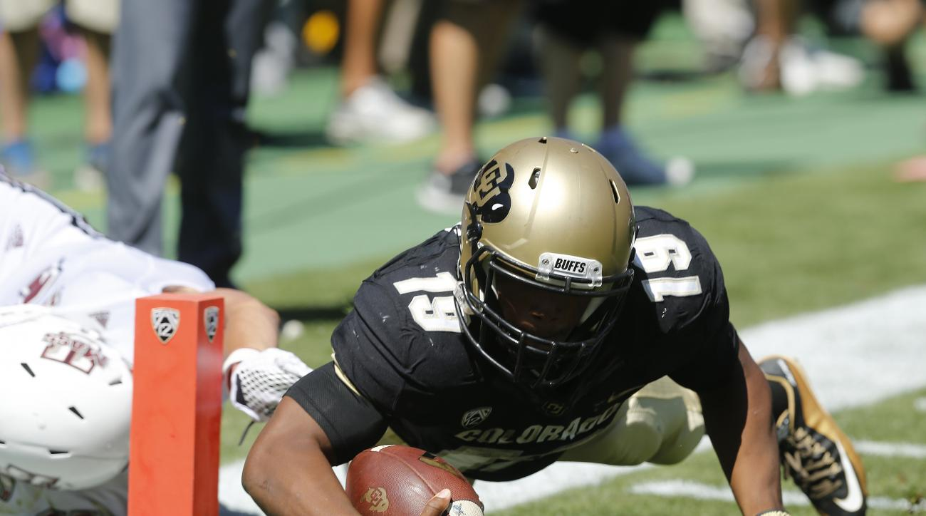 Colorado tailback Michael Adkins II dives in for a touchdown, in the first half of an NCAA college football game against Massachusetts, Saturday, Sept. 12, 2015, in Boulder, Colo. (AP Photo/Brennan Linsley)