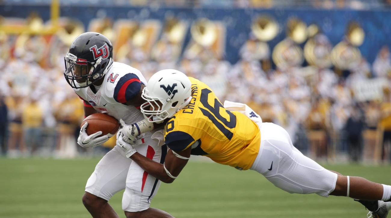 West Virginia cornerback Terrell Chestnut (16) tackles Liberty running back D.J. Abnar (2) during the first half of an NCAA college football game, Saturday, Sept. 12, 2015, in Morgantown, W.Va. (AP Photo/Raymond Thompson)