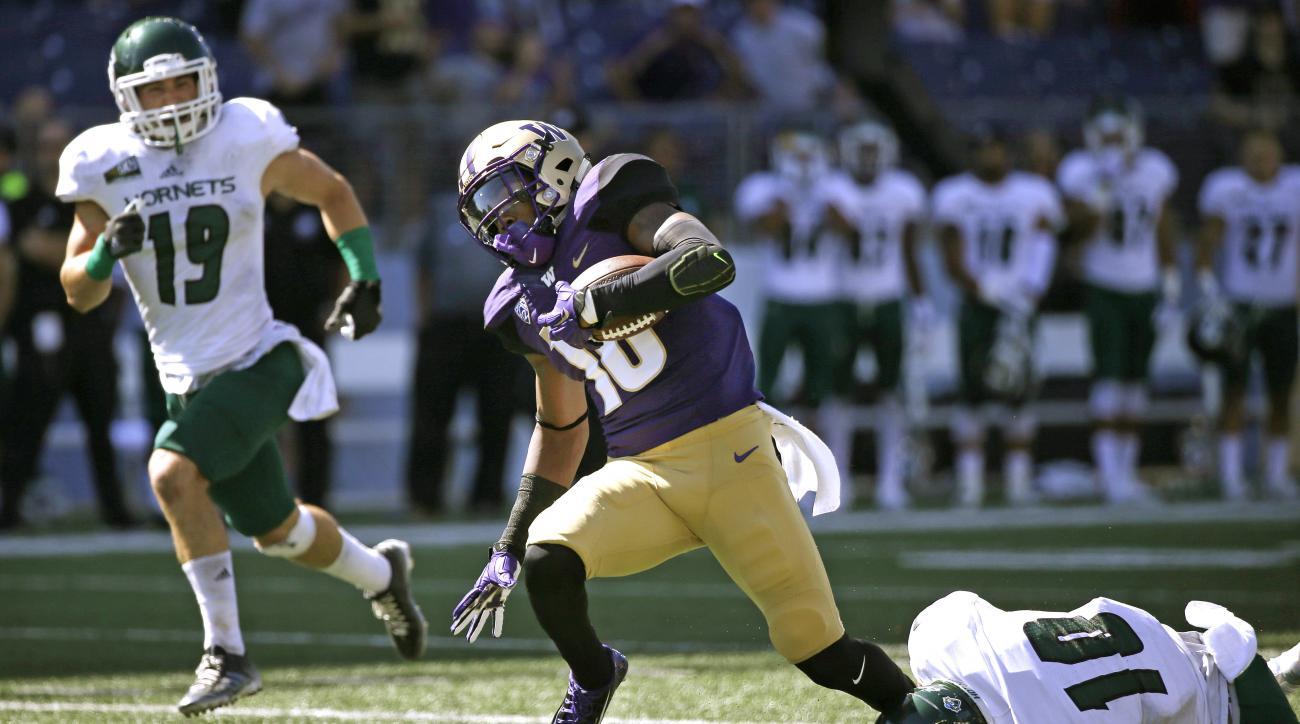 Washington's Marvin Hall, center, escapes a tackle on his scoring reception and run from Sacramento State's Austin Clark (10) as Nick Crouch (19) follows in the second half of an NCAA college football game Saturday, Sept. 12, 2015, in Seattle. Washington