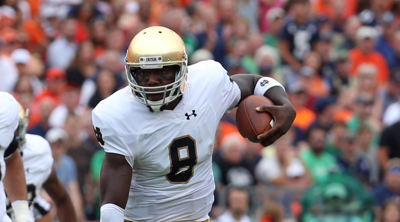 Notre Dame quarterback Malik Zaire (8) leaps over Virginia defenders during an NCAA college football game Saturday, Sept. 12, 2015, in Charlottesville, Va. (AP Photo/Andrew Shurtleff)