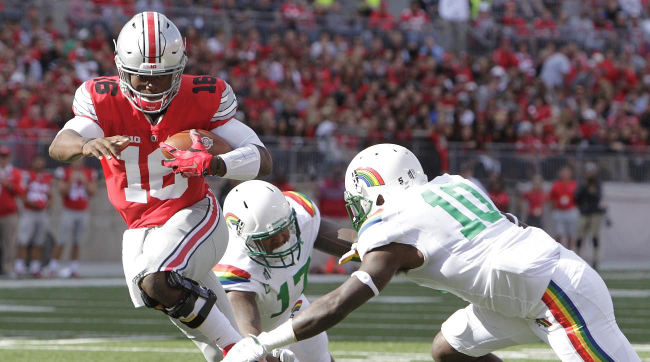 Ohio State quarterback J.T. Barrett, left, cuts upfield between Hawaii defenders Lance Williams, center, and Marrell Jackson during the second quarter of an NCAA college football game Saturday, Sept. 12, 2015, in Columbus, Ohio. (AP Photo/Jay LaPrete)