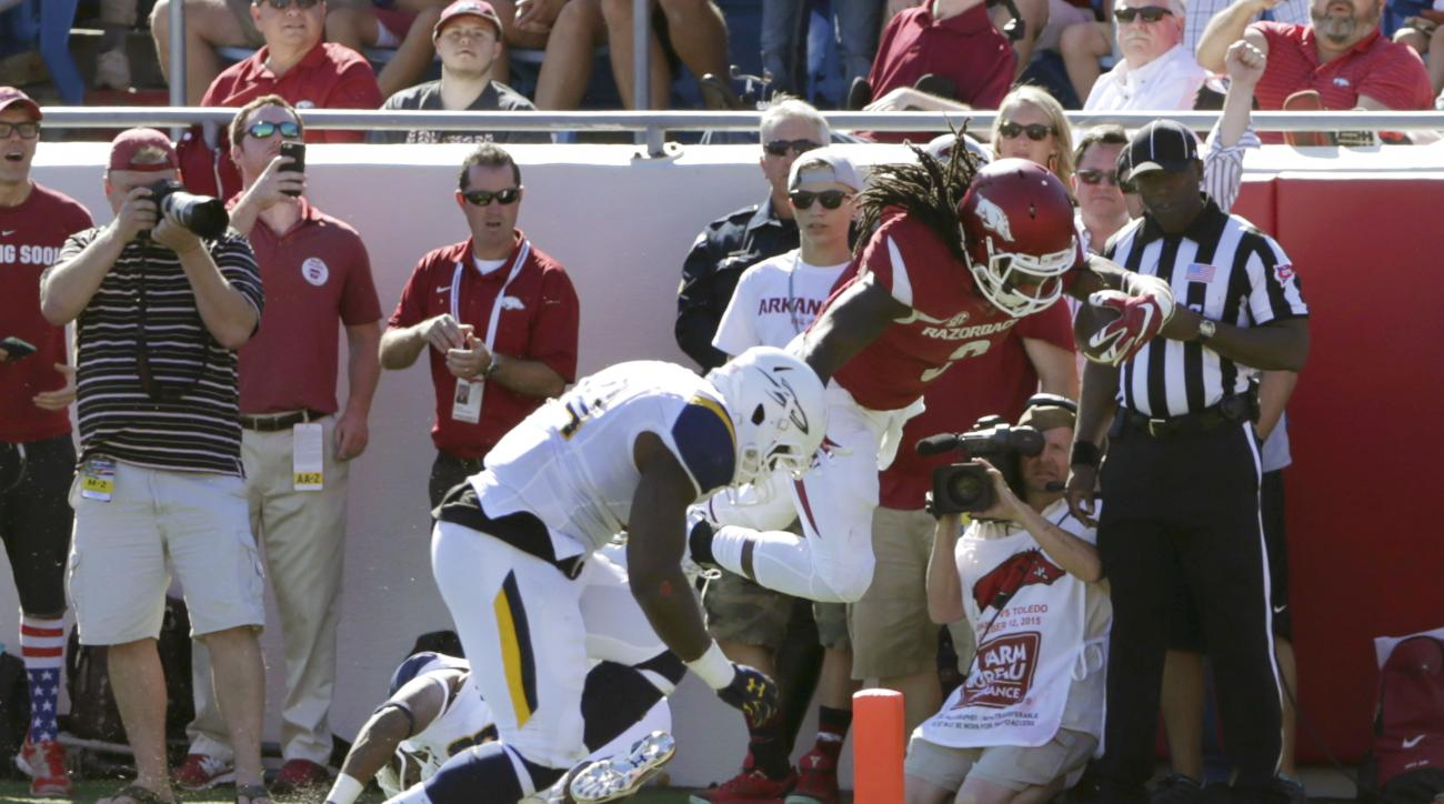 Arkansas running back Alex Collins (3) leaps into the end zone to score as he is tackled by Toledo linebacker Jaylen Coleman in first half of an NCAA college football game in Little Rock, Ark., Saturday, Sept. 12, 2015. (AP Photo/Danny Johnston)