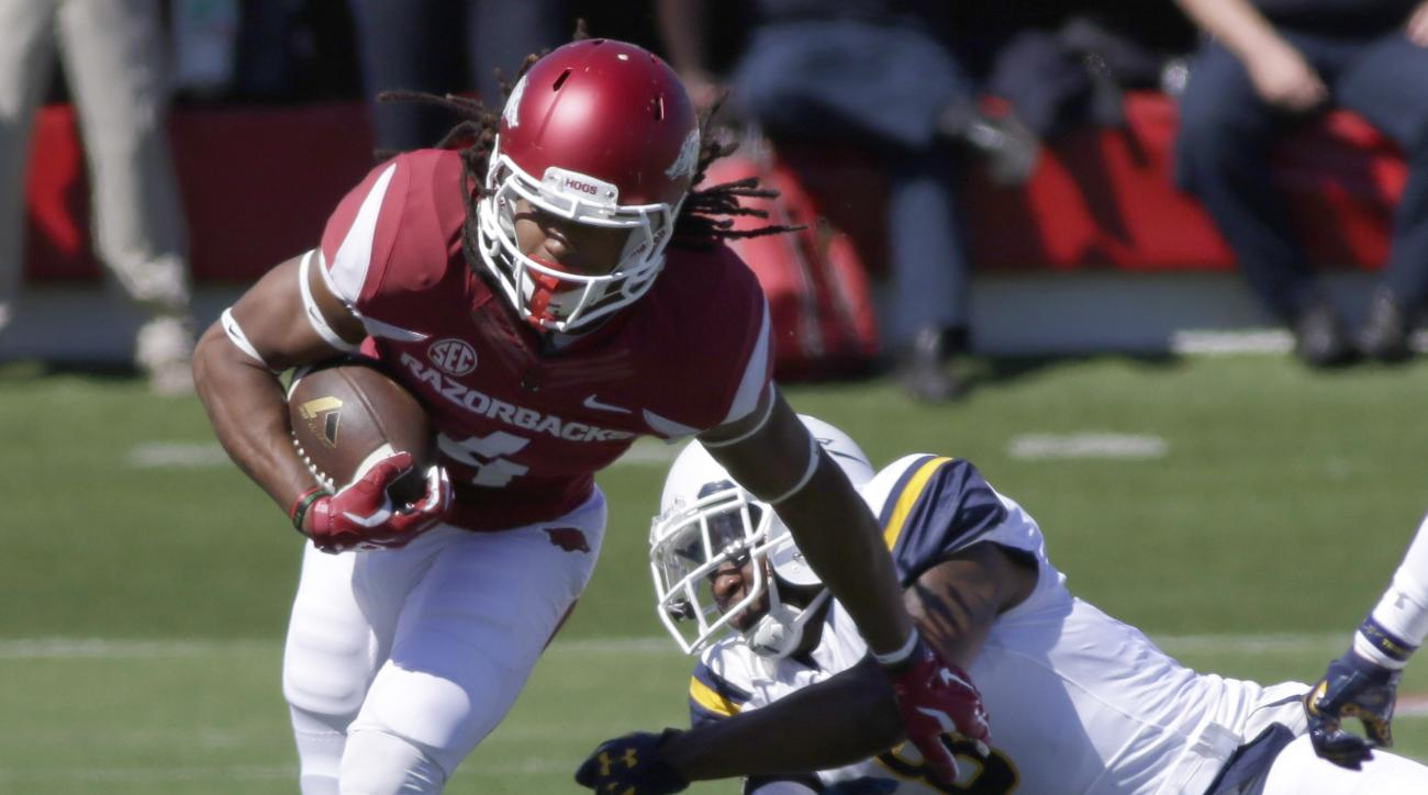 Arkansas wide receiver Keon Hatcher (4) breaks a tackle by Toledo safety Chaz Whittaker in first quarter of an NCAA college football game in Little Rock, Ark., Saturday, Sept. 12, 2015. (AP Photo/Danny Johnston)