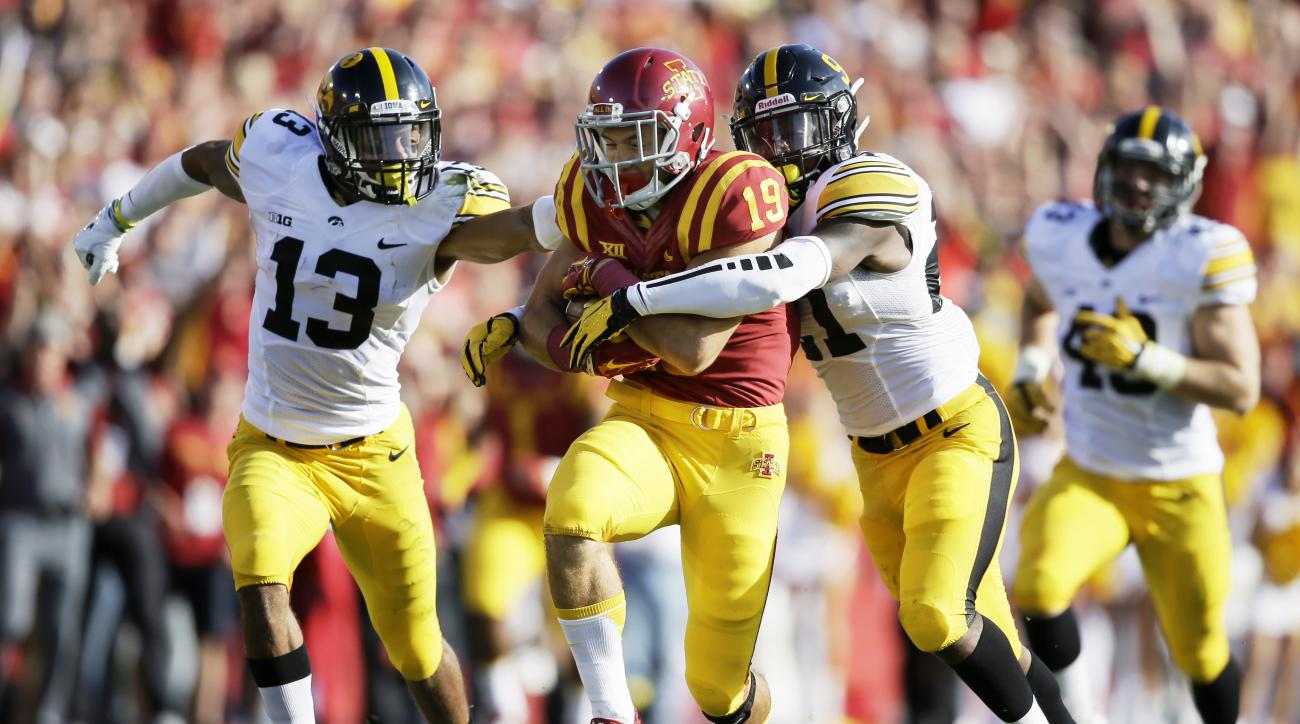 Iowa State wide receiver Trever Ryen (19) runs from Iowa defenders Greg Mabin, left, and Jordan Lomax, right, after making a reception during the first half of an NCAA college football game, Saturday, Sept. 12, 2015, in Ames, Iowa.  (AP Photo/Charlie Neib