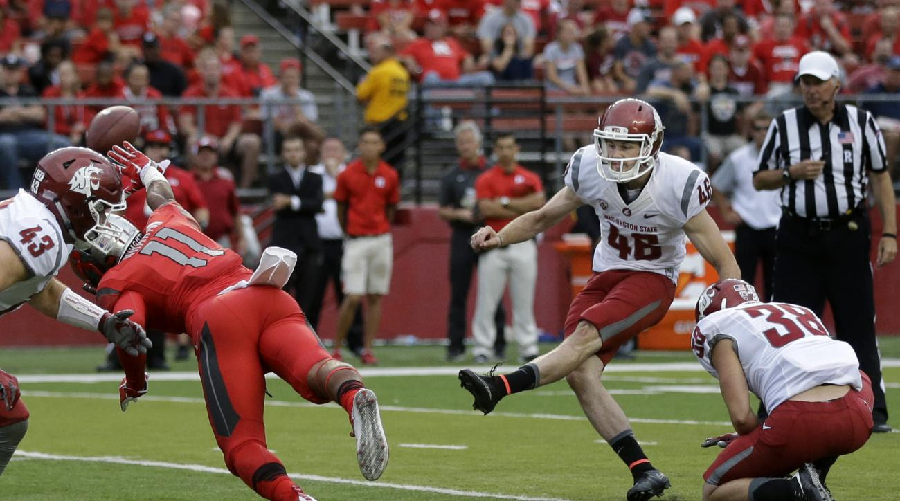 Rutgers defensive back Isaiah Wharton (11) gets a hand up to block a point after attempt by Washington State Erik Powell (46) during the second half of an NCAA college football game, Saturday, Sept. 12, 2015, in Piscataway, N.J. (AP Photo/Mel Evans)