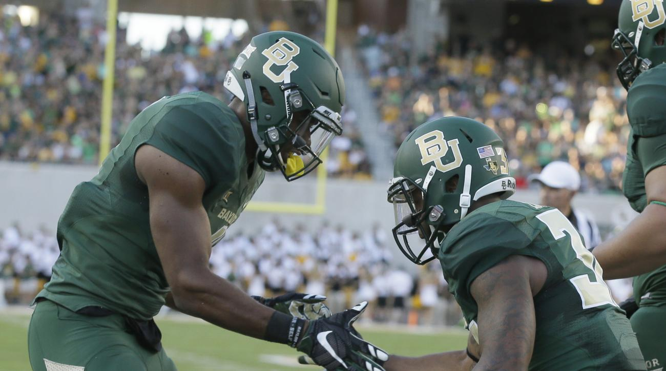 Baylor running back Shock Linwood (32) celebrates his touchdown with teammate Jay Lee, left, during the first half of an NCAA college football game against Lamar, Saturday, Sept. 12, 2015, in Waco, Texas. (AP Photo/LM Otero)