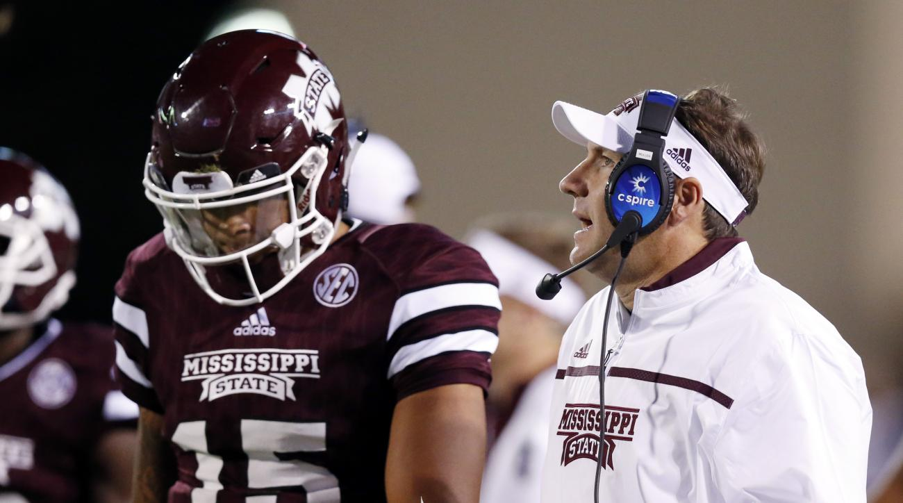 Mississippi State quarterback Dak Prescott (15) listens to his coach Dan Mullen during the first half of an NCAA college football game against LSU in Starkville, Miss., Saturday, Sept. 12, 2015. (AP Photo/Rogelio V. Solis)