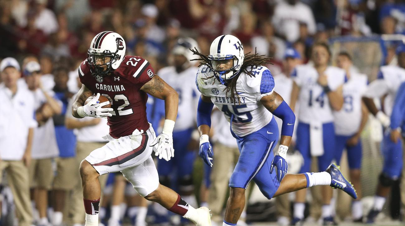 South Carolina running back Brandon Wilds (22) rushes for a first down as Kentucky linebacker Josh Forrest (45) gives chase in the second half of an NCAA college football game Saturday, Sept. 12, 2015, in Columbia, S.C. Kentucky won 26-22. (AP Photo/John