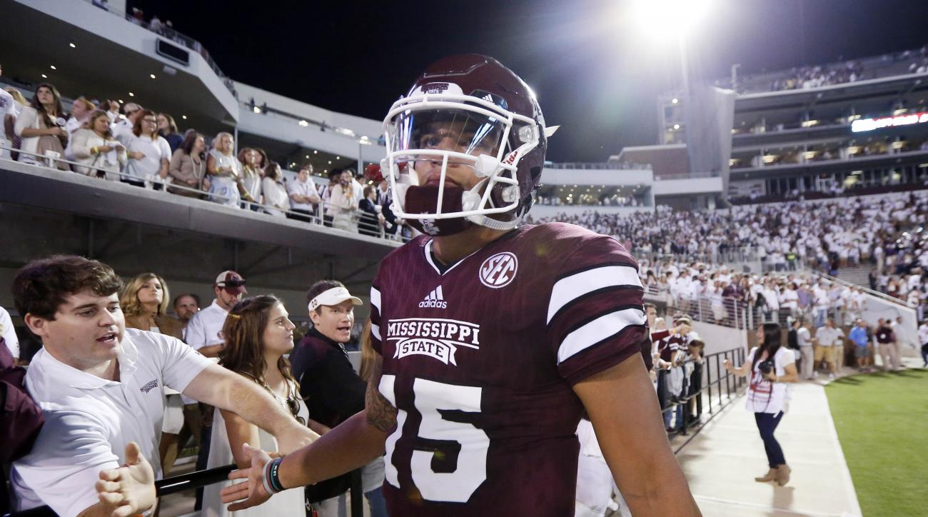FILE - In this Saturday, Sept. 12, 2015, file photo, a disappointed Mississippi State quarterback Dak Prescott (15) slaps hands with fans after their loss to LSU in an NCAA college football game at Davis Wade Stadium in Starkville, Miss. Prescott has had