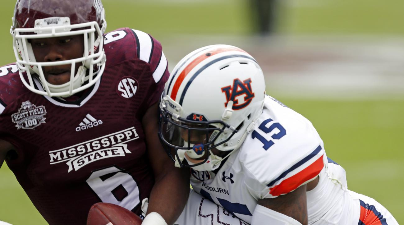 FILE - In this Oct. 11, 2014, file photo, Mississippi State tight end Malcolm Johnson (6) holds on to a pass as he is tackled by Auburn defensive back Joshua Holsey (15) in the first half of an NCAA college football game in Starkville, Miss. Holsey tore h