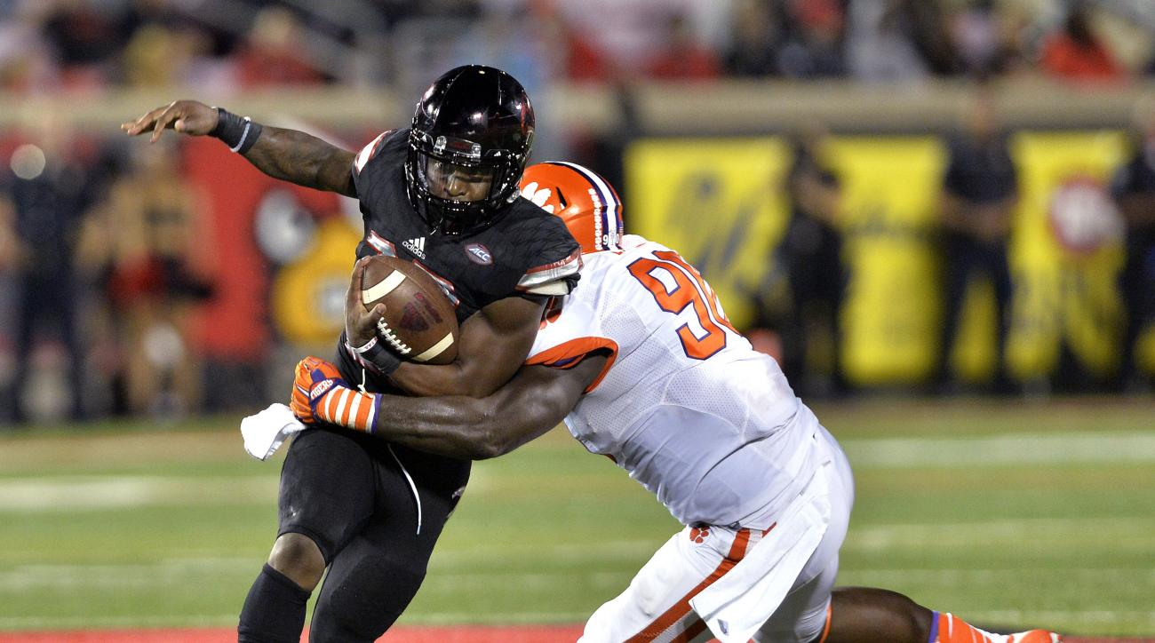 Louisville's Brandon Radcliff (23) is tackled by Clemson's Kevin Dodd (98) during the second half of an NCAA college football game in Louisville, Ky., Thursday, Sept. 17, 2015. Clemson defeated Louisville 20-17. (AP Photo/Timothy D. Easley)