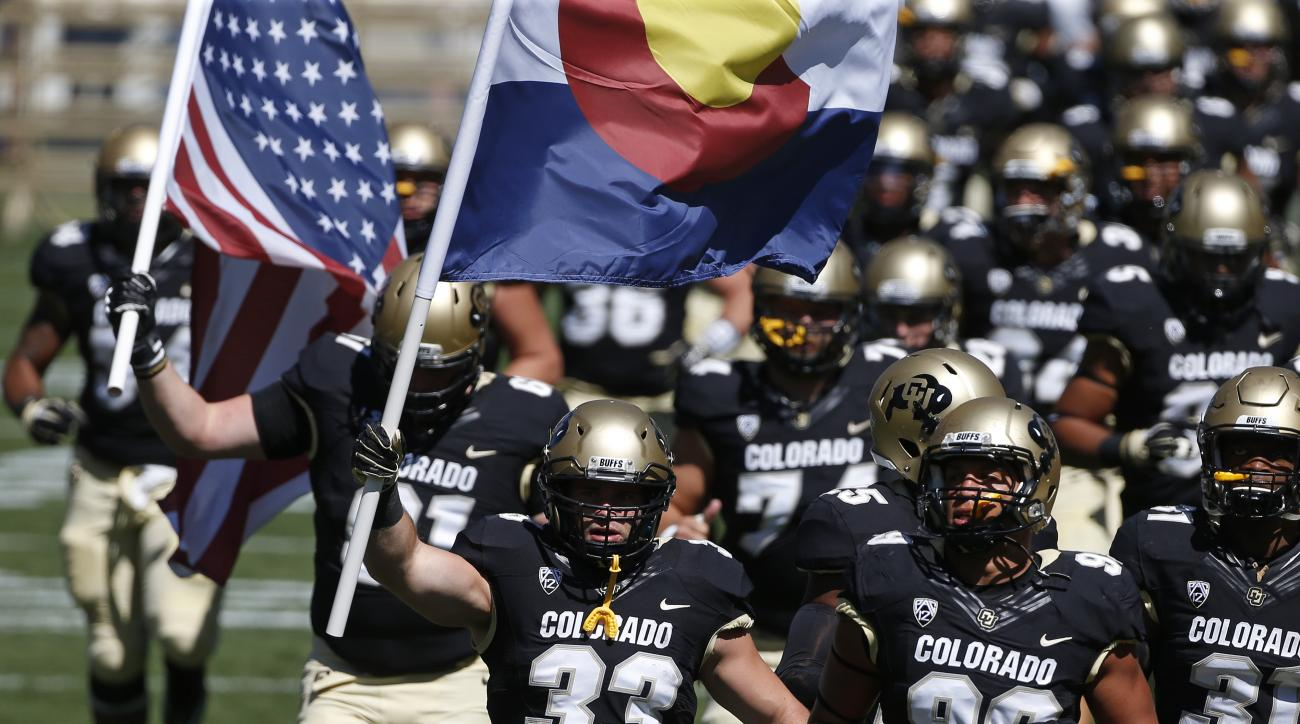 In this Sept. 12, 2015 photo, Colorado fullback Jordan Murphy, front left, carries a Colorado state flag as he runs on to the field with teammates before the start of an NCAA college football game against Massachusetts, in Boulder, Colo. On July 20, 2012,