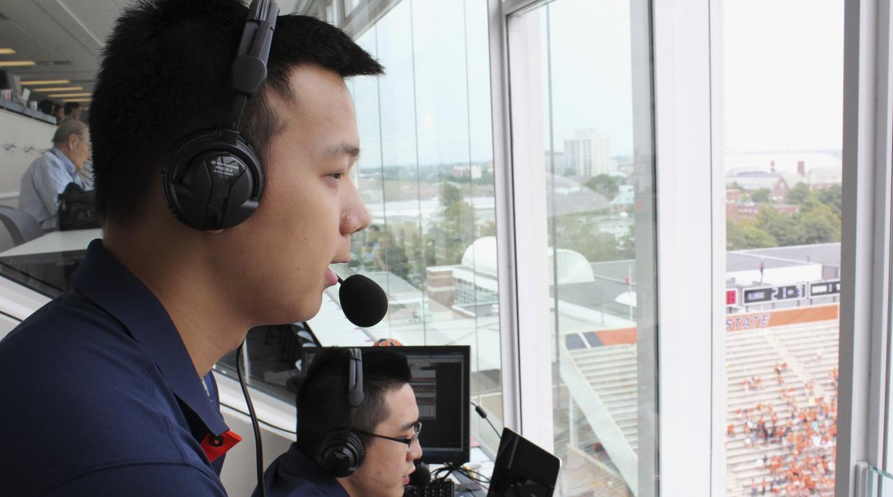In this Sept. 5, 2015 photo, David He, left, and Bruce Lu broadcast a University of Illinois NCAA college football game from Memorial Stadium in Champaign, Ill. The two Illinois students are broadcasting Illini football games online in Mandarin Chinese th