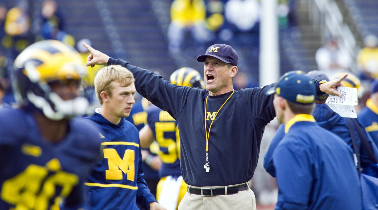 Michigan head coach Jim Harbaugh directs his players during warmups before an NCAA college football game against UNLV in Ann Arbor, Mich., Saturday, Sept. 19, 2015. (AP Photo/Tony Ding)