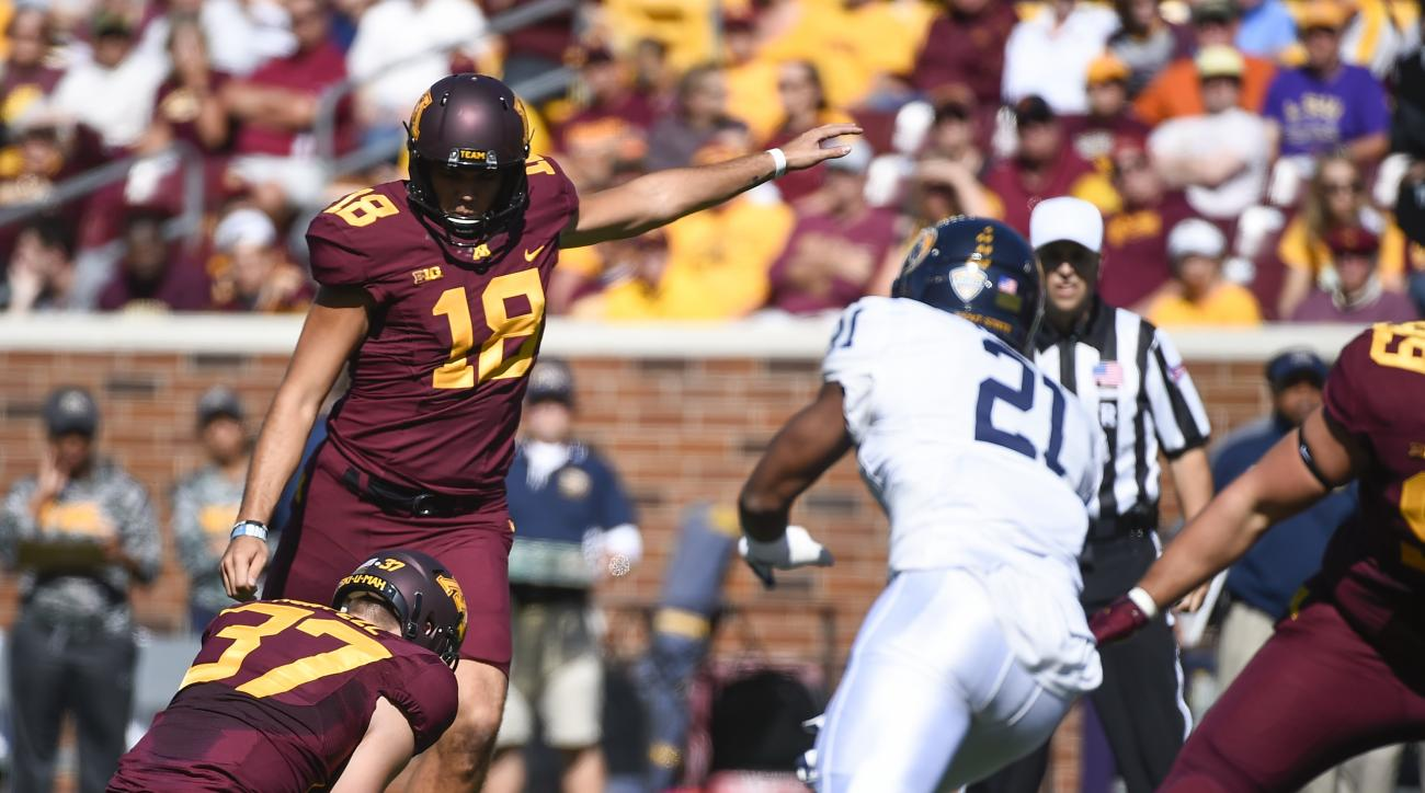 Minnesota kicker Ryan Santoso, left, makes a 42 yard field goal as the ball is held by Minnesota punter Peter Mortell and as Kent State defensive back Demetrius Monday, right, tries to block during the first half of an NCAA college football game on Saturd