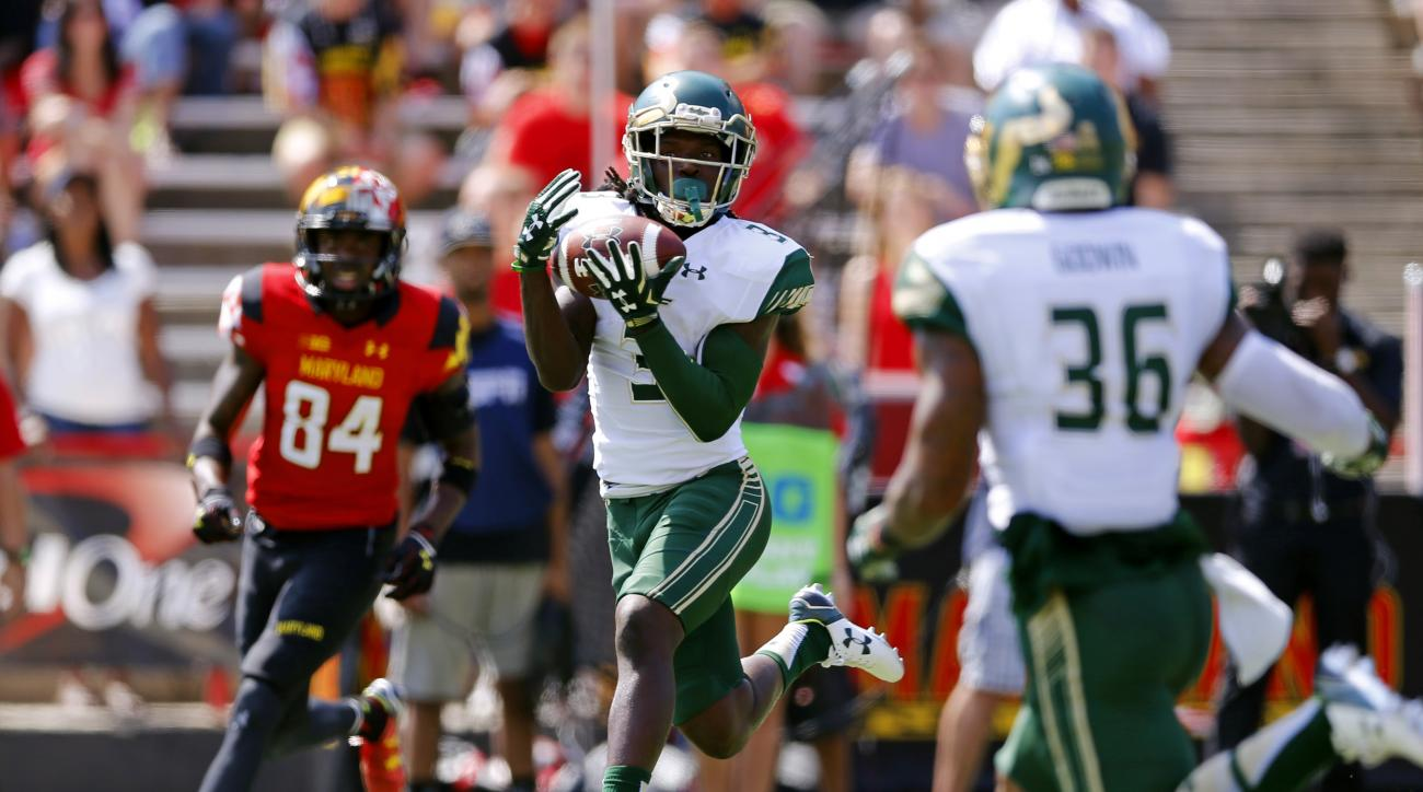 South Florida cornerback Deatrick Nichols, center, intercepts a pass in between Maryland wide receiver Amba Etta-Tawo, back left, and teammate Nate Godwin in the first half of an NCAA college football game, Saturday, Sept. 19, 2015, in College Park, Md. (