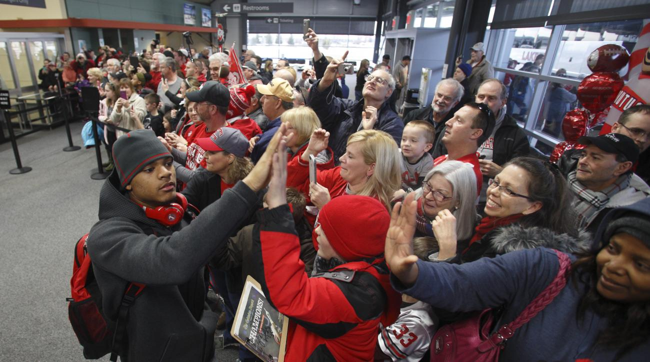 Ohio State corner back Damon Webb left, greets fans as he and his teammates arrive at Rickenbacker International Airport in Groveport, Ohio, Tuesday, Jan. 13, 2015, following a National Championship win over Oregon in Dallas, Texas. (AP Photo/Paul Vernon)