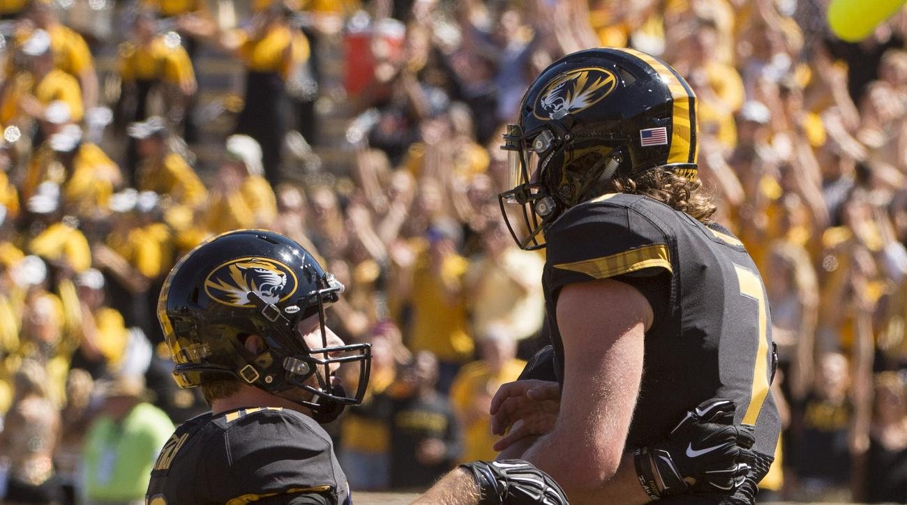 Missouri quarterback Maty Mauk, left, celebrates with teammate Wesley Leftwich, left, after Mauk scored a touchdown during the third quarter of an NCAA college football game against Connecticut, Saturday, Sept. 19, 2015, in Columbia, Mo. Missouri won the