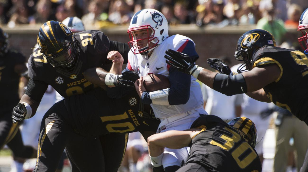 Connecticut quarterback Bryant Shirreffs, center, is gang tackled by Missouri's Rickey Hatley, right, Josh Augusta, left, Michael Scherer (30) and Kentrell Brothers (10) during the fourth quarter of an NCAA college football game Saturday, Sept. 19, 2015,