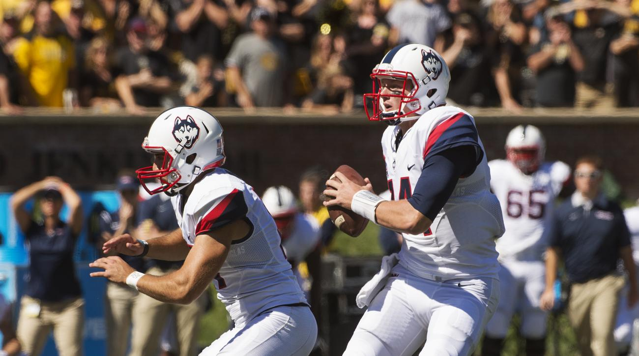 Connecticut's Tim Boyle, right, fakes the handoff to kicker Bobby Puyol, left, before Boyle threw an interception late during the fourth quarter of an NCAA college football game against Missouri. Saturday, Sept. 19, 2015, in Columbia, Mo. Missouri won the