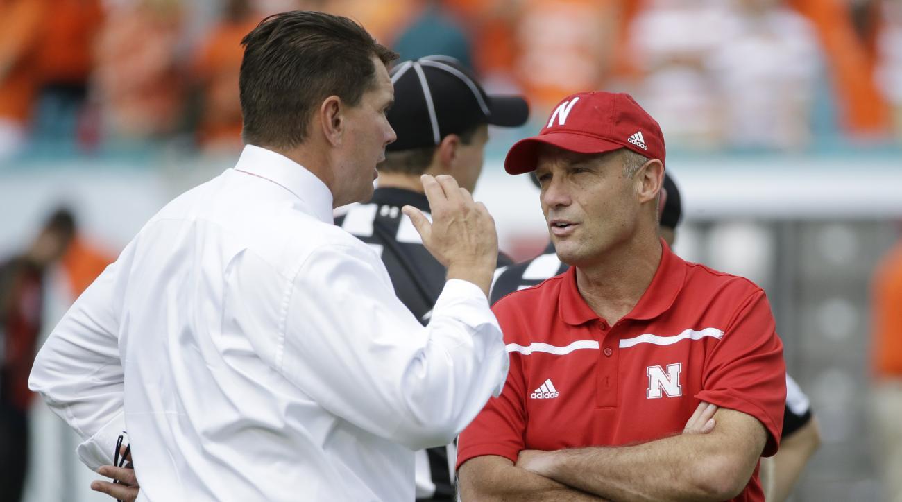 Miami head coach Al Golden, left, and Nebraska head coach Mike Riley talk before the start of an NCAA college football game, Saturday, Sept. 19, 2015 in Miami Gardens, Fla. (AP Photo/Wilfredo Lee)
